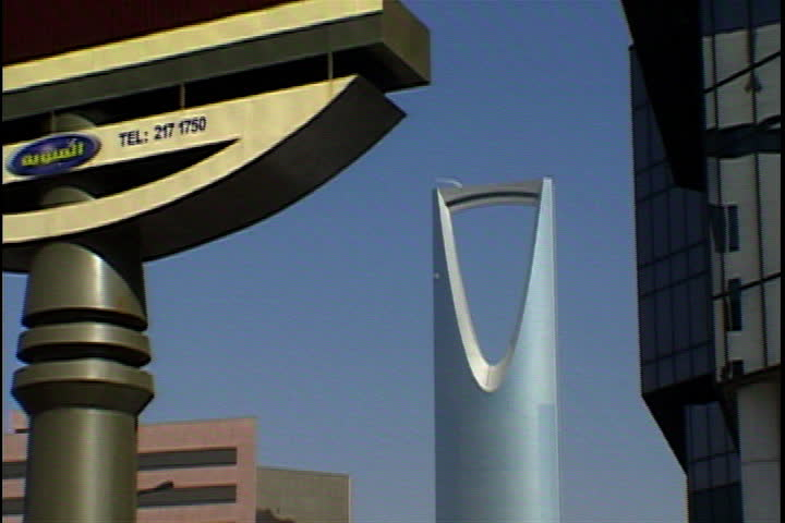 RIYADH, SAUDI ARABIA - SEPTEMBER 29, 2002: Window washers hanging on side of Kingdom Tower, camera zooms far back to WS of square.