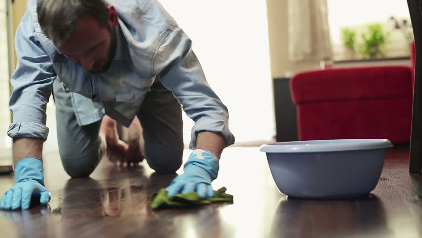 Tired unhappy young man cleaning wooden floor in home