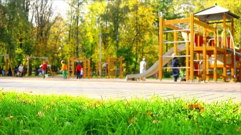 Children have fun  on playground in park on sunny weekend day, focus on foreground, dolly camera movement.