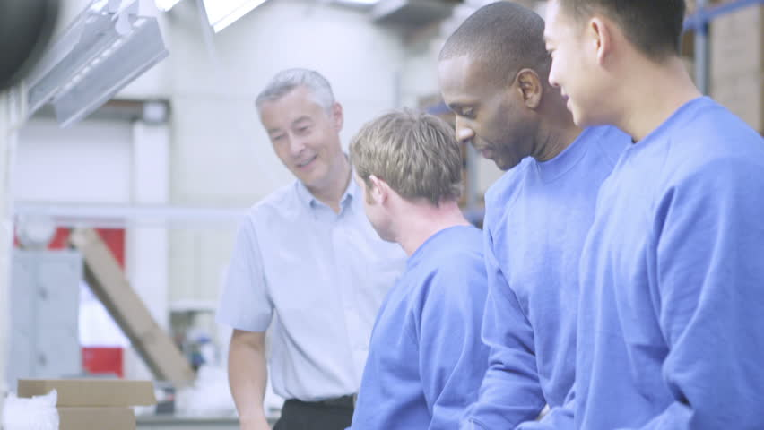 Happy male factory staff of mixed ethnicity working together on an assembly line, making electrical light fittings. | Shutterstock HD Video #4409489