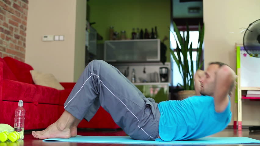 Young man exercising, doing sit-ups in home