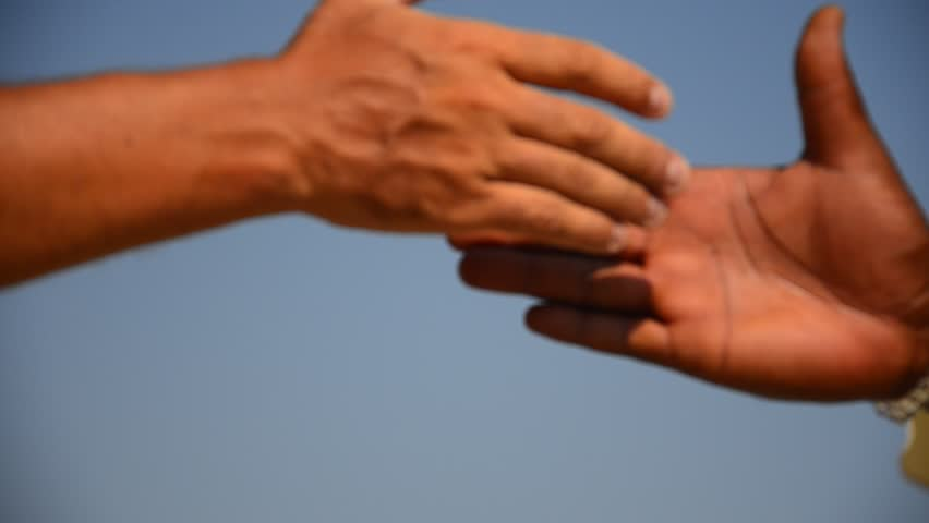 HD Handshake. HD1080 blurred background of handshake of two unrecognizable black and white men on blue sky. close up view. Tripod.