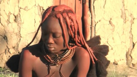 KAMANJAB - MARCH 28:  African native tribes - Young Himba woman plays with her child on March 28, 2012 in Kamanjab, Namibia.
