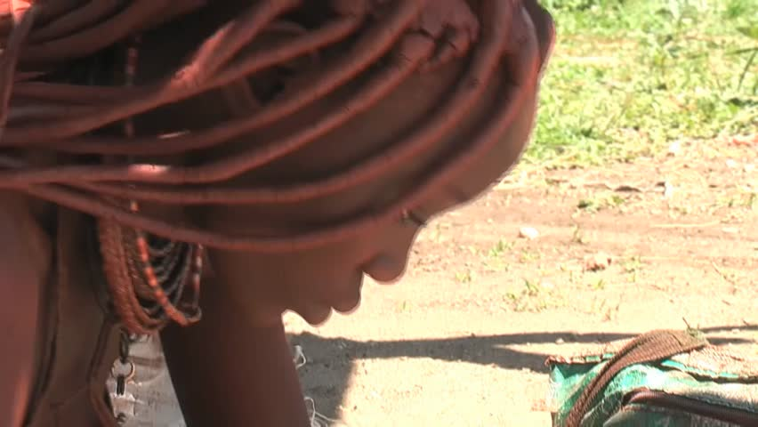 KAMANJAB - MARCH 28: African native tribes - Young Himba woman produces jewelery   on March 28, 2011 in Kamanjab, Namibia.