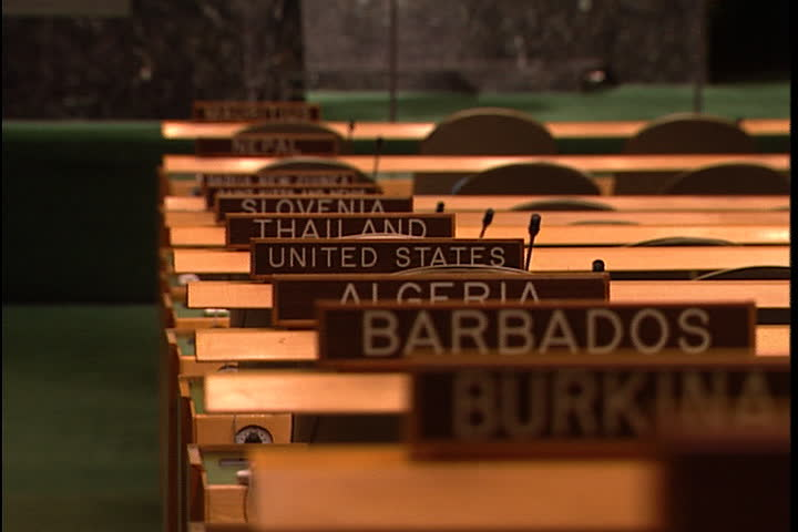 NEW YORK CITY - FEBRUARY 11, 1999: MS row of wooden name signs on desks in  the United Nations General Assembly hall, camera zooms in to CU of signs for Algeria, United States and Thailand.