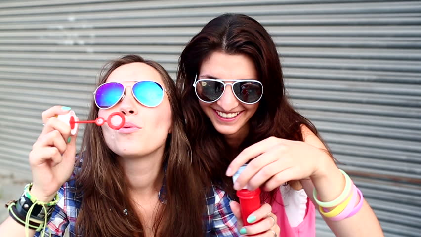 Cheerful hipster girls with sunglasses having fun making bubbles | Shutterstock Video #4435724