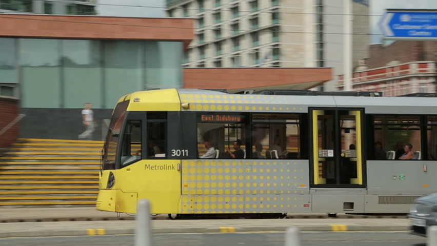 MANCHESTER, LANCASHIRE/ENGLAND - JULY 26: Pan of Metrolink tram as it passes G-MEX centre on July 26, 2013 in Manchester. Metrolink is a light rail system in Greater Manchester.