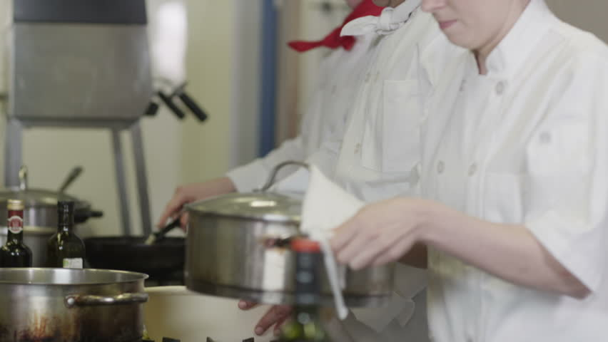 Team of professional chefs preparing and cooking food in a commercial kitchen. In slow motion. #4449536