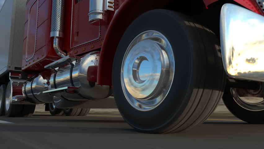 18 Wheel Truck on the road with sunset in the background. Large delivery truck is moving towards setting sun. Closeup on a moving wheel.