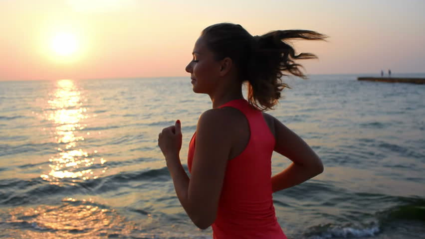 a young woman with a slender figure is engaged in gymnastics at sea at sunrise. She makes a run along the sea coast. sequence camera stabilizer shots.