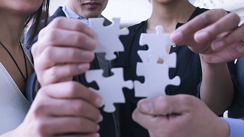 Making the pieces fit. Business people bring jigsaw puzzle together.