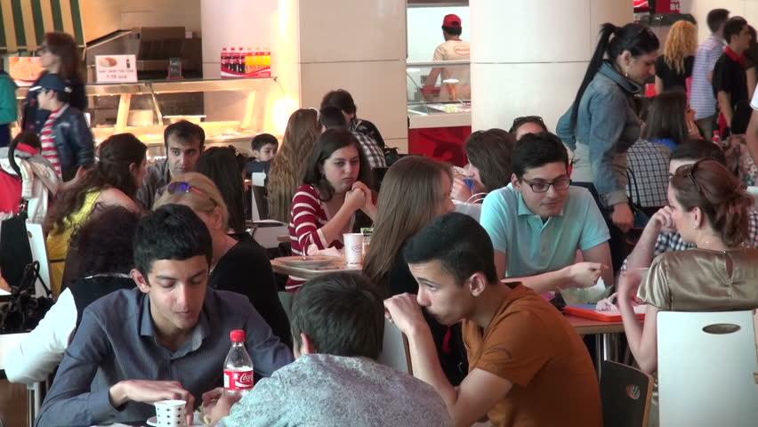 BAKU, AZERBAIJAN - 10 MAY 2013: Young people are enjoying a fast food lunch in an impressive food court in Baku, Azerbaijan