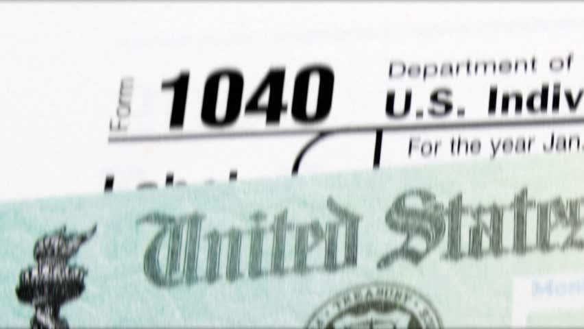 Zooming out shot of 1040 income tax return form with federal tax return check