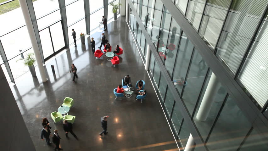 Business people dancing down the stairs inside a modern office building.