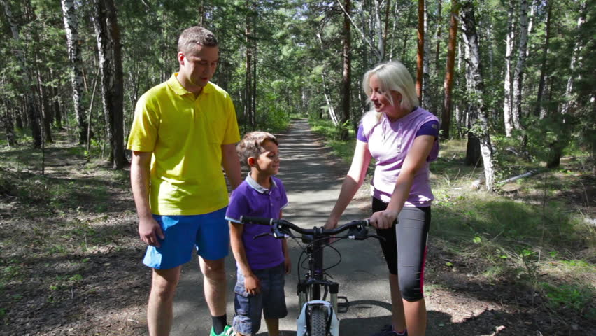 Happy kid learning how to ride a bike with the help of his parents