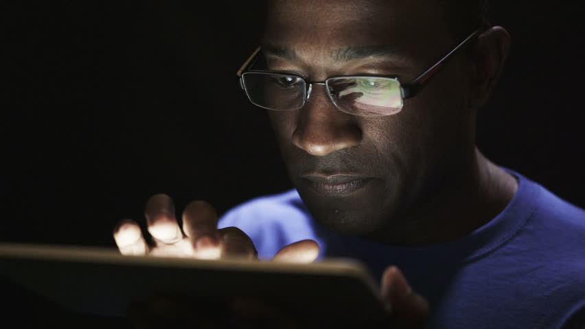 Close up of young black man reading his tablet in the dark. Black background.