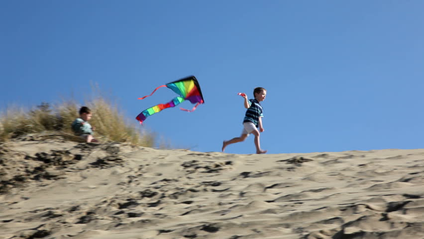 Young boy running with kite
