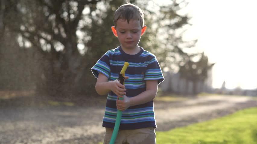 Young boy spraying hose