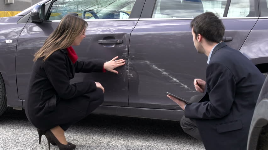 Woman and insurance agent discussing car damage
