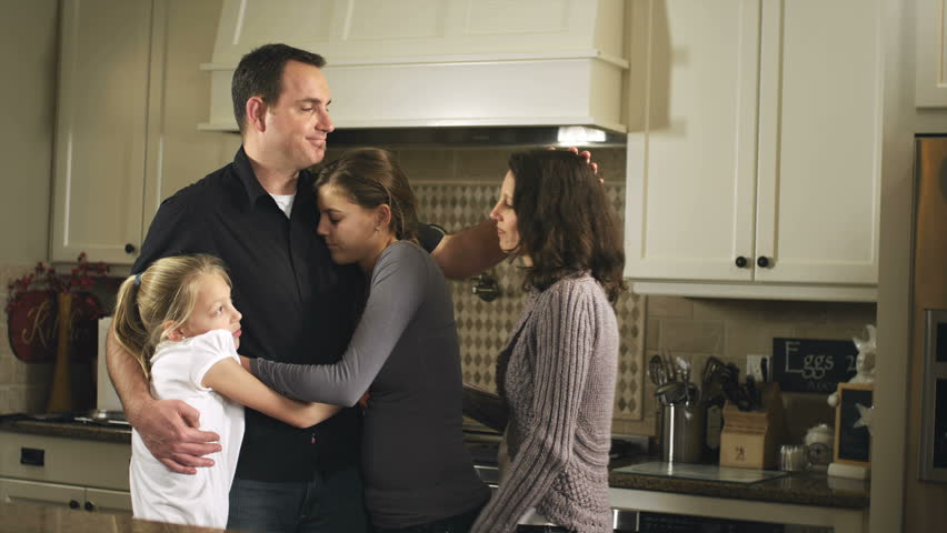 The females of a family walk into the kitchen and give their father/husband a big family hug. Medium shot.
