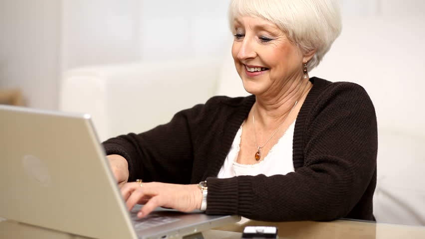 Senior woman using laptop and cell phone