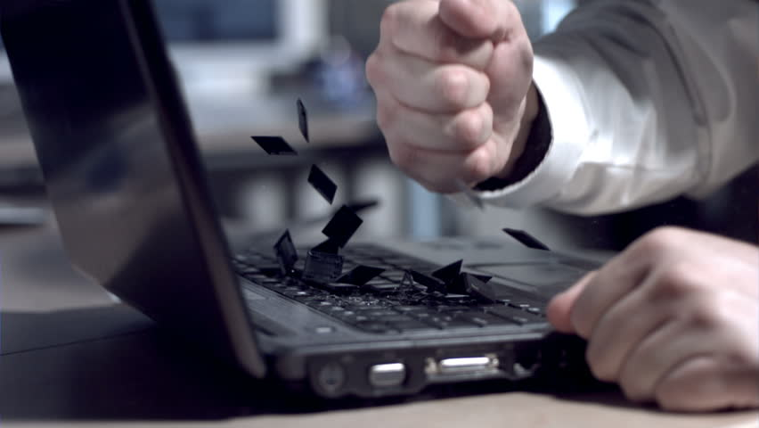 Businessman smashing laptop with fist, slow motion