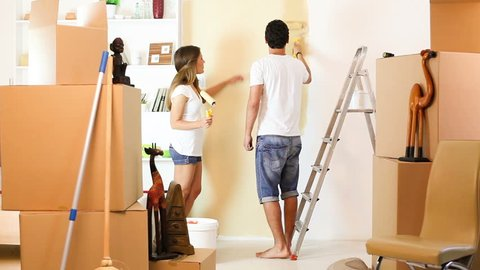 Young couple decorate their new apartment.Moving in new home.Man are paint the wall.