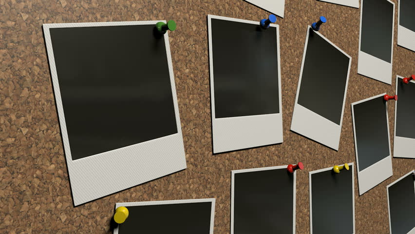 A pan across of a perspective view of a collection of many blank polaroid films pinned to a cork bulletin board with various colored pushpins