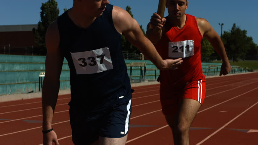 Athletes pass the baton in a track relay