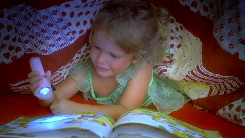A cute little girl is hiding under the bed sheet in the bedroom in order to read her favorite book with a torch. She wants to sleep, so she closes the book.