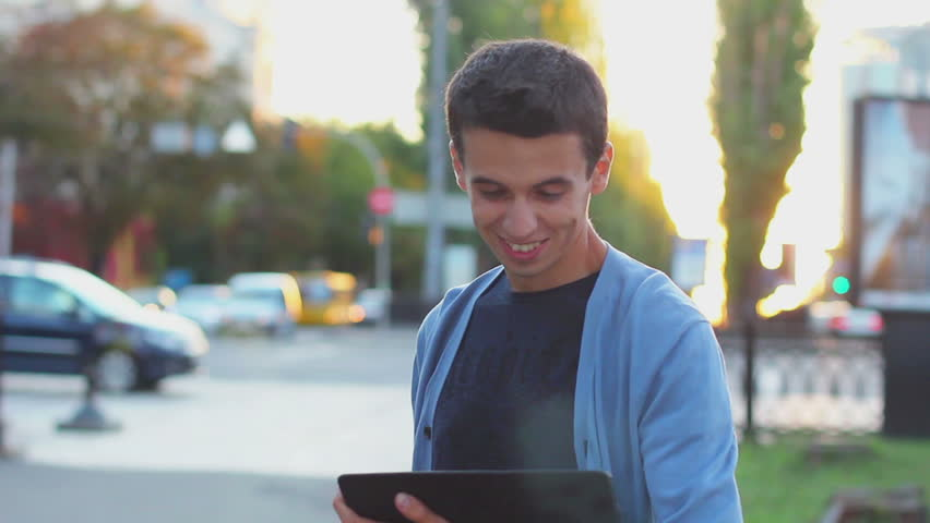 Young male browsing tablet pc computer smiling at camera outdoor