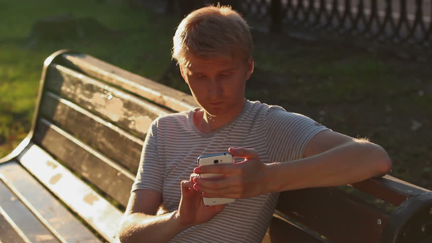 Blond male writing sms message to girlfriend sitting in park