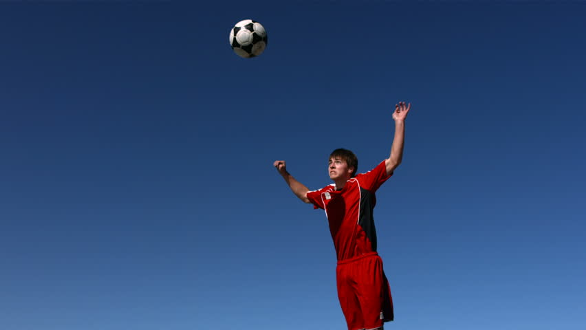 Soccer player heads ball, slow motion