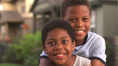 Older brother gets on younger brothers back and they both look at the camera. Close up shot