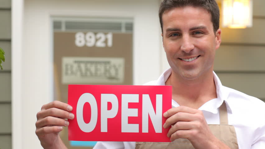 Portrait of small business owner with open sign