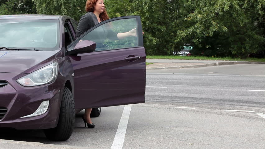 Woman a driver getting out of own car