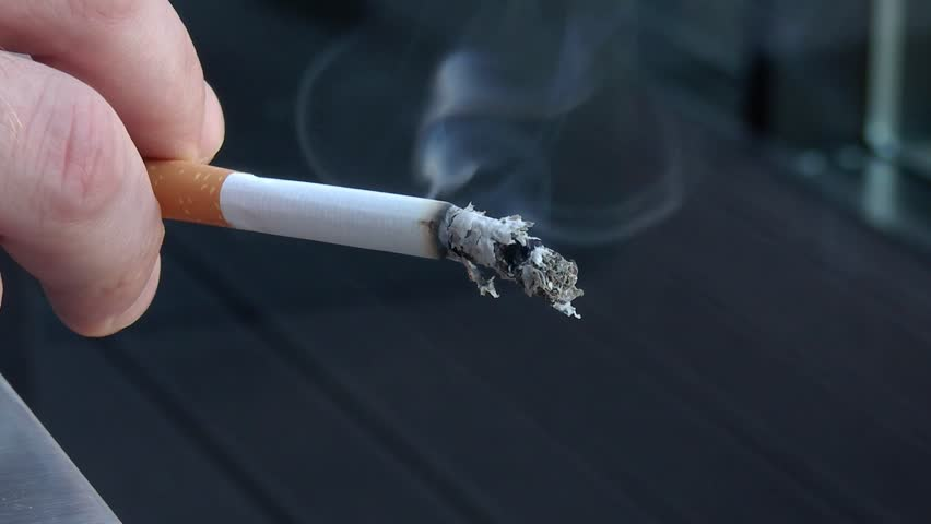Close up of a human hand holding a smoking cigarette.../I´ll take a break