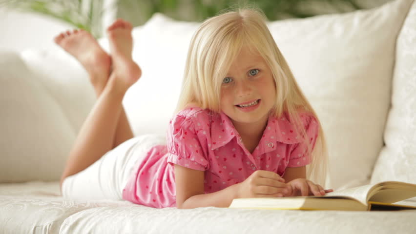 Beautiful little girl lying on sofa reading book and smiling at camera