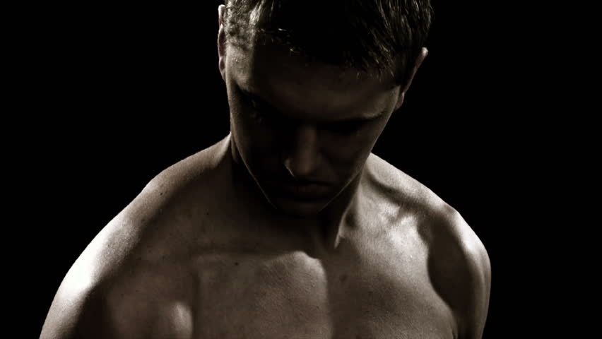 Close shot of a muscular man lifting weights in the shadows