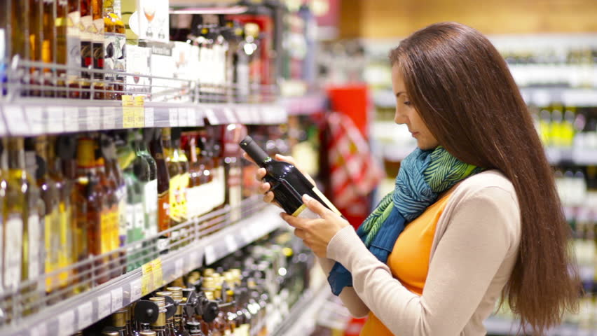 Smiling young woman choosing a bottle of red wine | Shutterstock HD Video #4623560