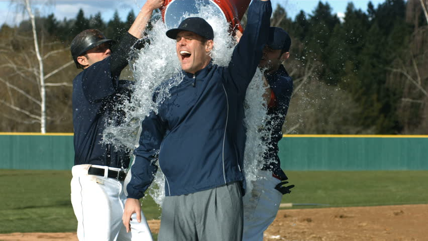 Baseball players pour cooler of water over coach, slow motion