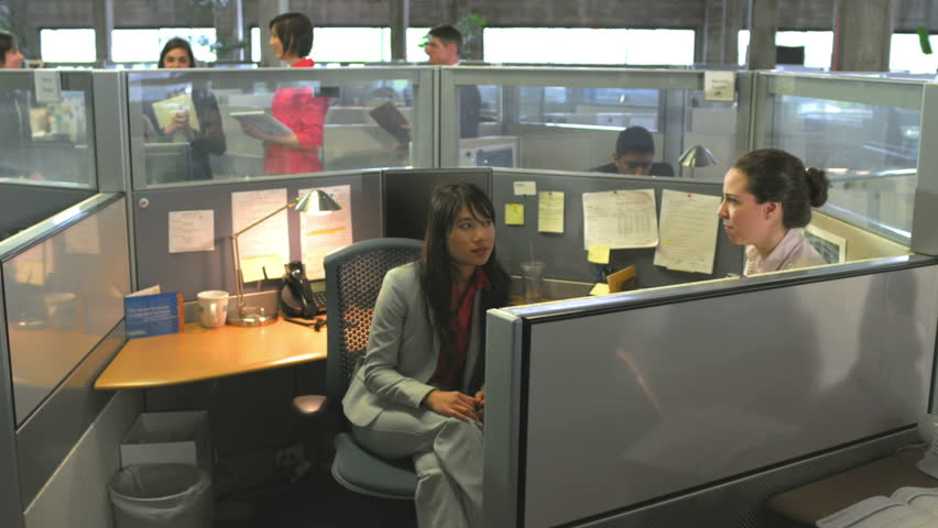 Dolly shot of various people having conversations in their cubicles. Wide shot.