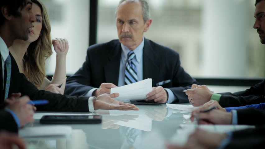 An older businessman leads a meeting at a large table