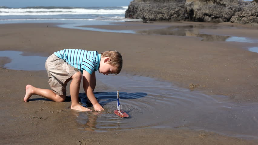 Young boy at beach playing with toy boat