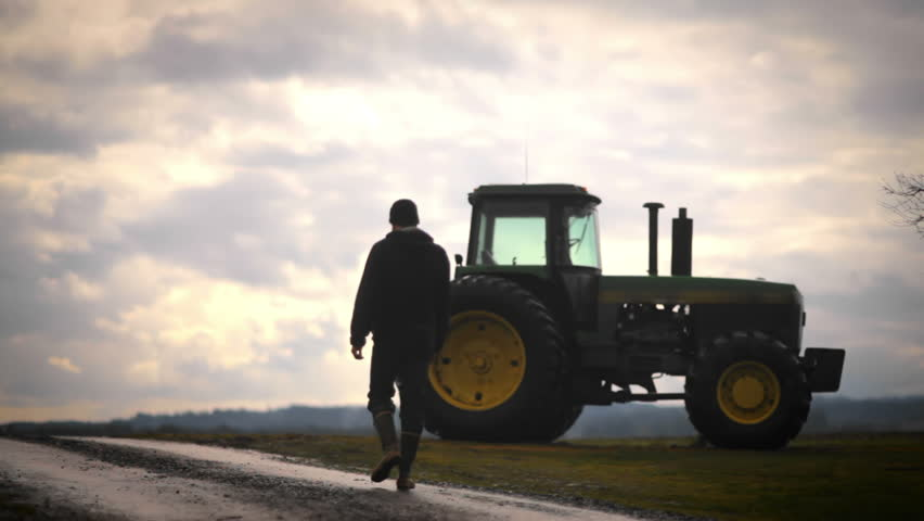 A farmer walks towards his tractor in the early morning while silhouetted  | Shutterstock HD Video #4642271