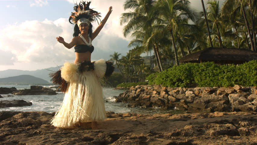 Polynesian dancer performs along rocky coastline, slow motion