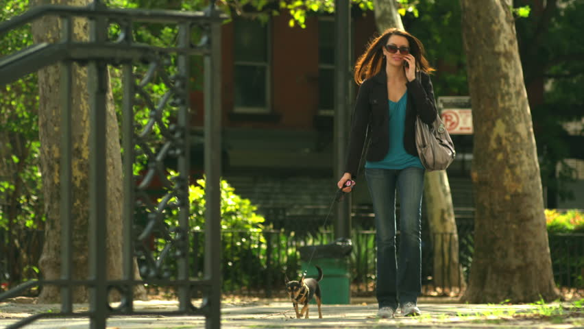 Young woman walks her dog and talks on the phone. Wide shot.