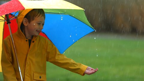 Young boy in rain with umbrella, slow motion