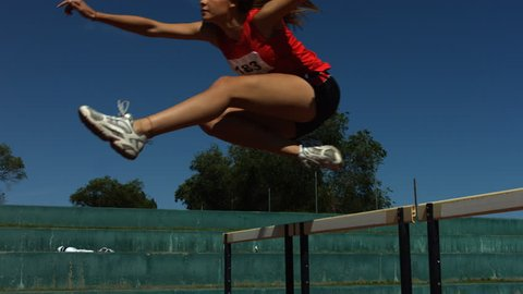Track athlete jumps over hurdle, slow motion