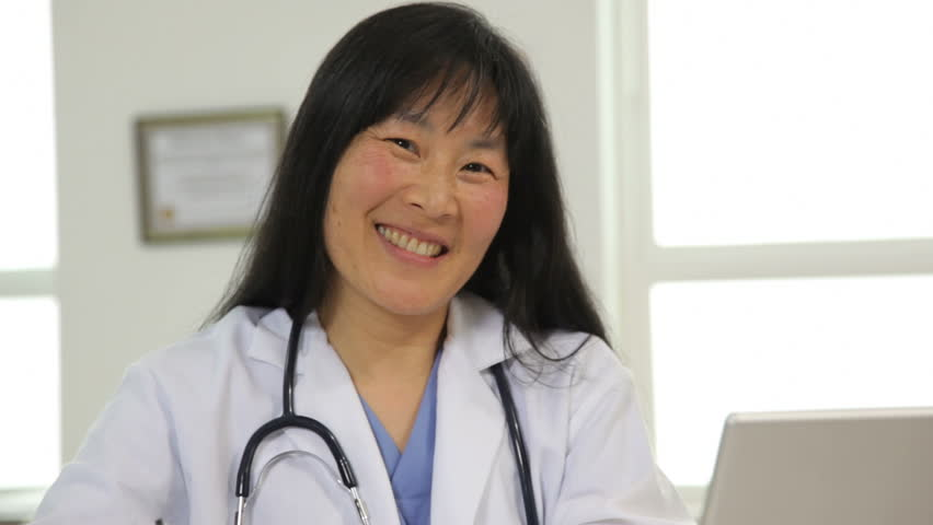 Portrait of female Asian doctor at desk
